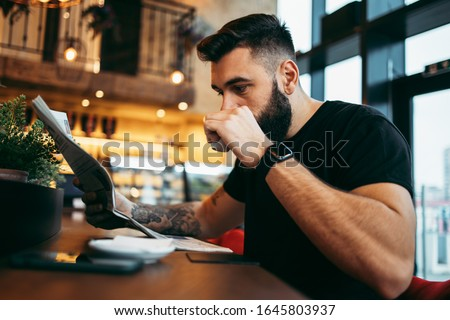 Young adult hipster man with a long beard sitting in modern cafe bar, reading newspapers and emotionally reacting.