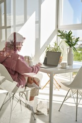 Young adult hipster teen girl school student with pink hair using laptop computer sitting at chair kitchen table behind glass working learning online at home office having morning breakfast. Vertical.