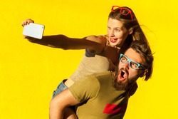 Young adult hipsters. Bearded man shout, freckled brunette woman wink, toothy smile and making selfie piggyback boy. Yellow background. Studio shot