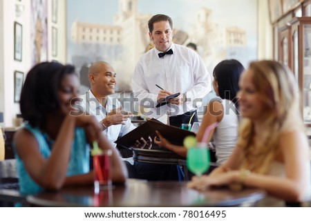 young adult hispanic couple dining out in restaurant and talking to waiter in bow tie. Horizontal shape, front view, waist up
