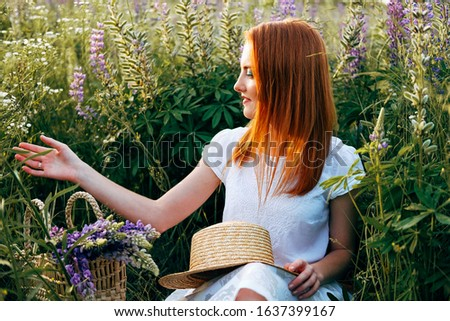 Young adult holding straw shopper bag with lupine flowers. Slow fashion concept. Waiting for her beloved person.
