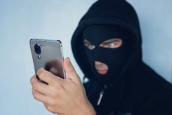 Young adult in black clothes with hidden face looks at smartphone screen. Ill-intended fraudster uses mobile. Fraudster calls. Mobile racket. Hacker hijacks by phone. Cellphone account fraud. Scam