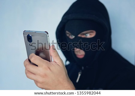 Young adult in black clothes with hidden face looks at smartphone screen. Ill-intended fraudster uses mobile. Fraudster calls. Mobile racket. Hacker hijacks by phone. Cellphone account fraud. Scam Foto stock ©