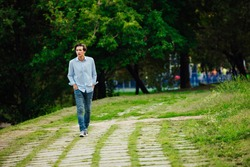 young adult in blue shirt and jeans walking alone in park