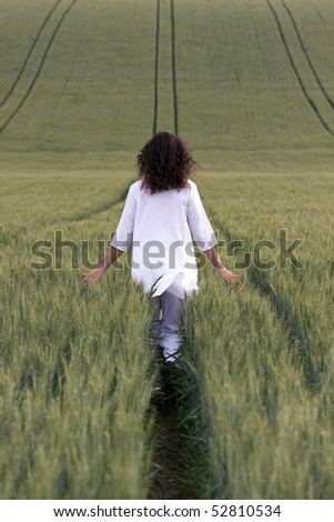 young adult is walking through field of cereal plant and let flow his thoughts.
