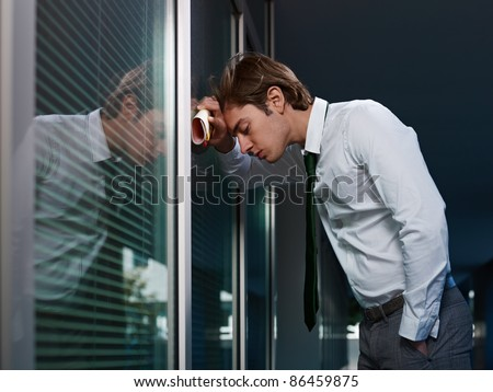 young adult italian business man banging his head against a window in office. Horizontal shape, copy space