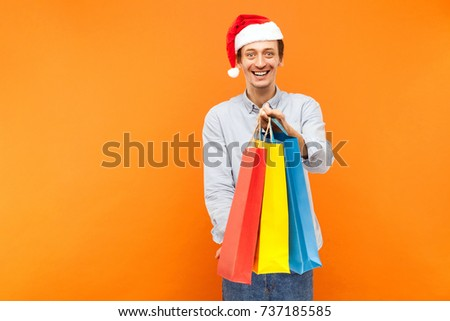 Young adult joyful man in Christmas red hat toothy smiling showing colorful packets at camera Studio shot on orange background