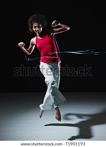 young adult latin american female jumping and playing with led lights doing streaks on black background. Vertical shape, full length, front view, copy space