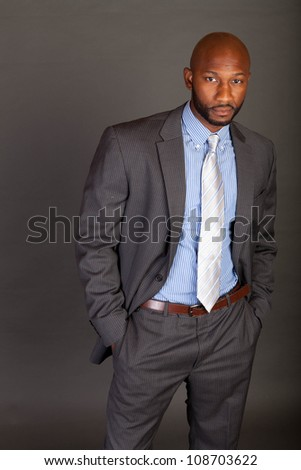 Young adult lifestyle shot of a black businessman dressed in a suit with his hands in his pockets looking confidently into the camera with a shaved head on a grey background