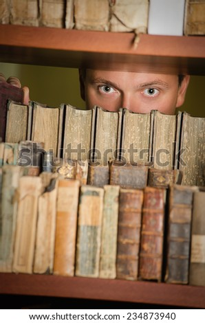 Young adult looking through library bookshelf