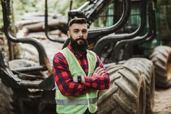 Young adult lumberjack or logger standing in front of huge bagger excavator in the woods and looking in the camera with crossed arms.