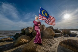 young adult Malaysian female waving Malaysia flag against blue sky in a windy day
