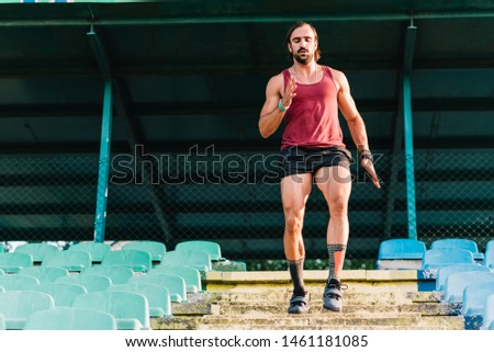 Young adult male athlete running stairs at stadium
