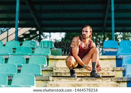 Young adult male athlete tying shoe at stadium stairs