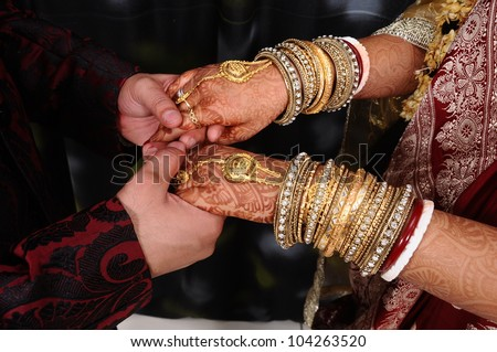 Young adult male groom and female bride holding hands.
