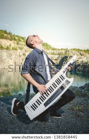Young adult male Playing energetic singing screaming a nature by the water lake, concept of freedom free lifestyle