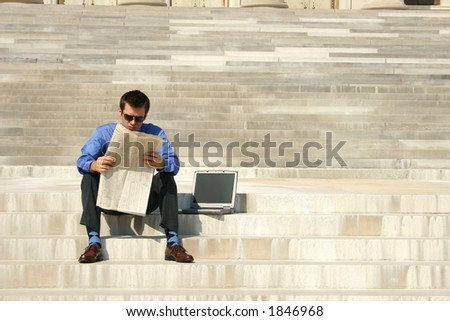Young adult male reading a newspaper on steps with a laptop computer next to him.