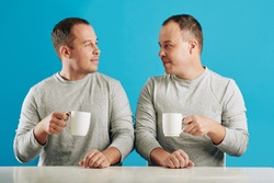 Young adult male twin siblings sitting at table looking at each other holding cups with coffee, blue background