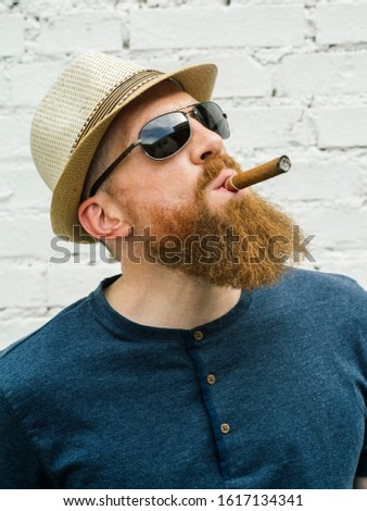 Young adult male wearing fedora and sunglasses smoking a cigar on the street.