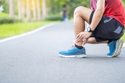 Young adult male with his muscle pain during running. runner man having leg ache due to Ankle Sprains or Achilles Tendonitis. Sports injuries and medical concept