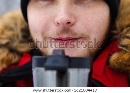 young adult man drinking coffee from refillable mug outdoors
