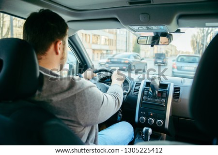 young adult man driving car by city streets using phone as navigation. lifestyle #1305225412