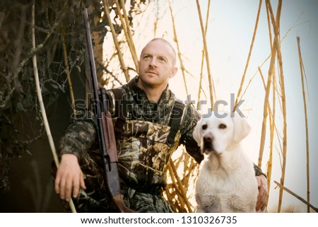 Young adult man duck shooting with a gun and his dog by a lake.