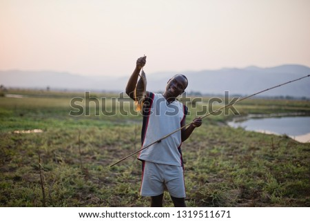 Young adult man holding a fish and rod beside a pond.