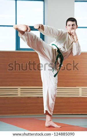 young adult man in kimono training taekwondo martial art at gym