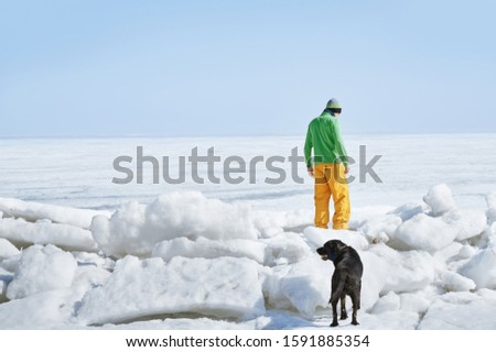 Young adult man outdoors with his dog exploring winter landscape