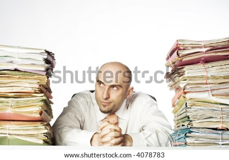 Young adult man sits between 2 large stacks of file folders. He has a smirking expression on his face.