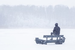 Young adult man sitting and resting on bench during blizzard in white winter day. Looking far away. Thinking about life. Spending time alone in nature. Back view.