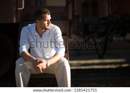 Young adult man sitting outside. #1285421755