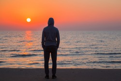Young adult man standing on sand and staring at small waves of sea and orange sunset. Peaceful atmosphere in summer evening. Back view. Empty place for text, quote or sayings on nature background.
