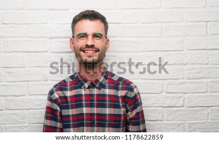 Young adult man standing over white brick wall with a happy face standing and smiling with a confident smile showing teeth #1178622859