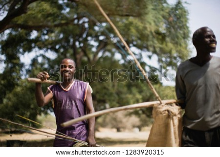 Young adult man with a mature adult man holding fishing rods.