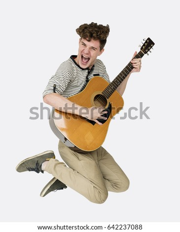 Young adult man with guitar smiling and jumping studio portrait #642237088