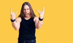 Young adult man with long hair wearing goth style with black clothes shouting with crazy expression doing rock symbol with hands up. music star. heavy music concept.