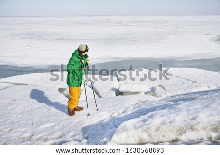 Young adult man with walking sticks outdoors exploring icy landscape
