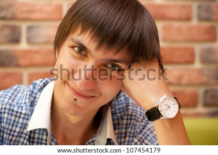 Young adult man with watch sitting at cafe