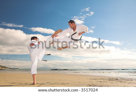 Young adult men practicing Karate on the beach. One is in a high kick and the other flying through the air (some movement on the edges)