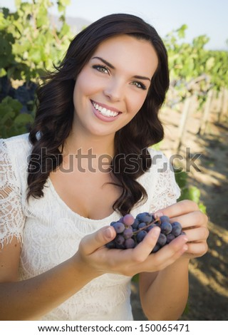 Young Adult Mixed Race Woman Enjoying The Wine Grapes in The Vineyard Outside.