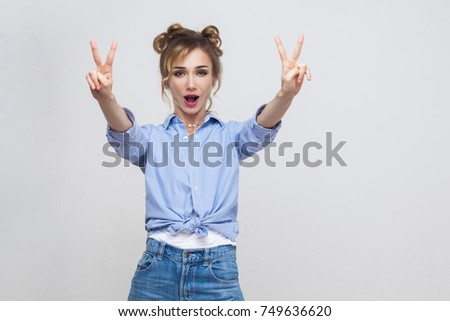 Young adult pretty beautiful blonde woman with blue dress and head band showing peace sign. Isolated studio shot on gray background. Studio shot, gray wall