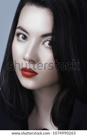 Young adult sexy lady with white skin red lips and black straight hairstyle. Mixed race Caucasian Asian female model isolated on gray background #1074990263