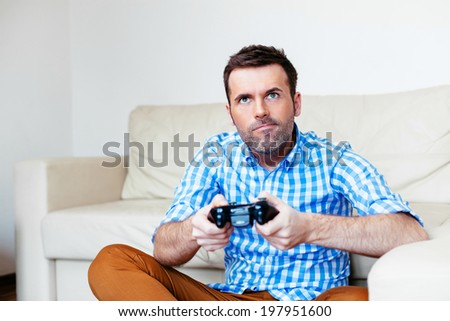 Young adult sitting on the floor and playing a game console
