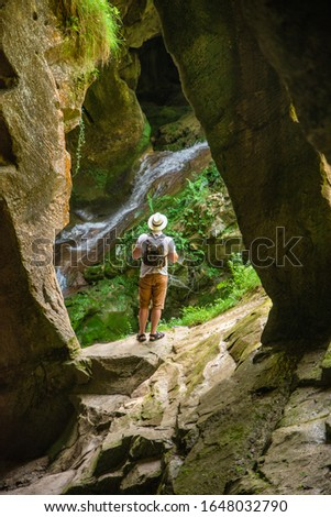 young adult strong man with backpack at cave entrance looking on sunlight