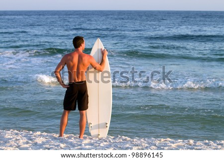 Young adult surfer stands by the shoreline holding his board looking out into the sea.