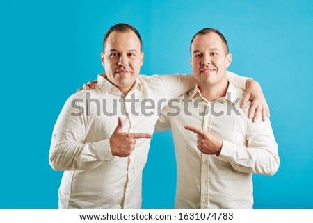 Young adult twin brothers standing against blue wall background pointing fingers at each other looking at camera smiling