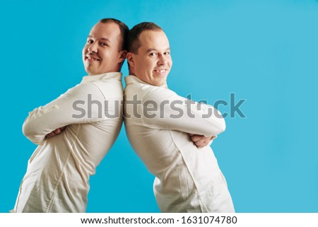 Young adult twin brothers standing back to back with arms crossed looking at camera, blue background