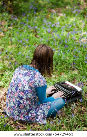 Young adult using a vintage typewriter in a forest of bluebells - stock photo